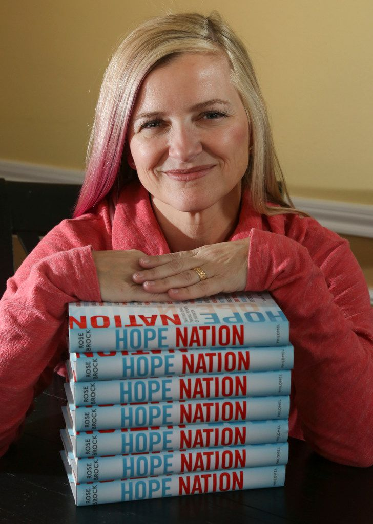Rose Brock, who is a professor of library science, poses with her new book, 'Hope Nation,' in her Grapevine  home. The book is a collection of essays by writers of young adult fiction, published by Penguin Random House.