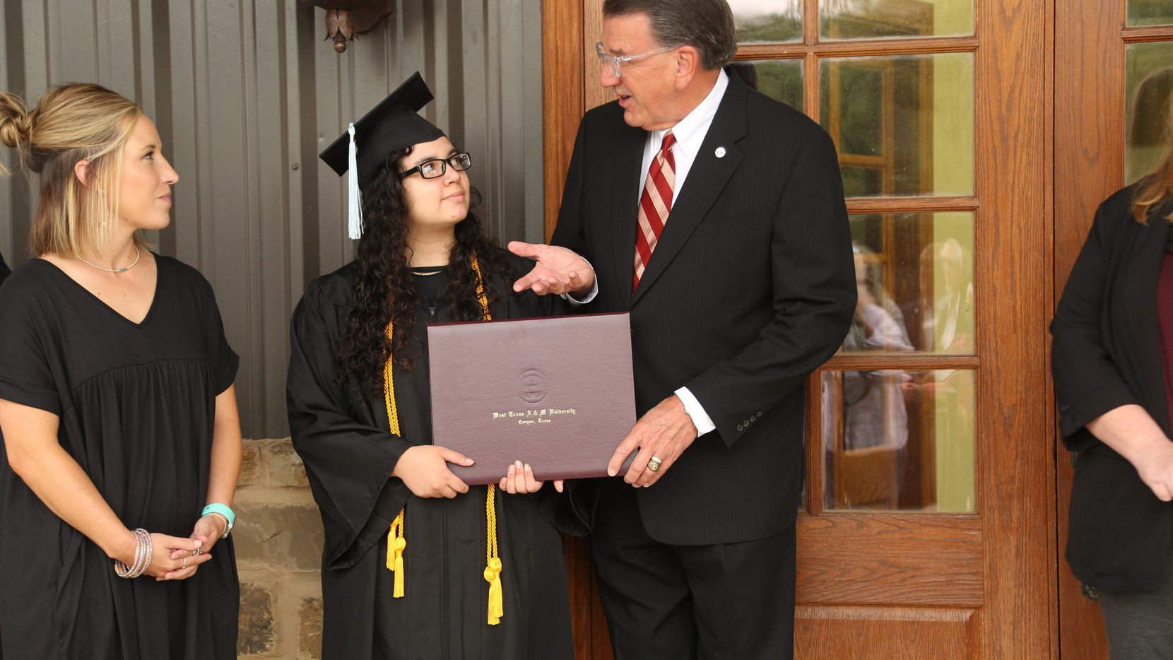 Morgan Martin, Roscoe ISD Dean of Continuing Education, left, celebrates the graduation of Amanda Sanchez, middle, with West Texas A&M University President Walter Wendler, right.