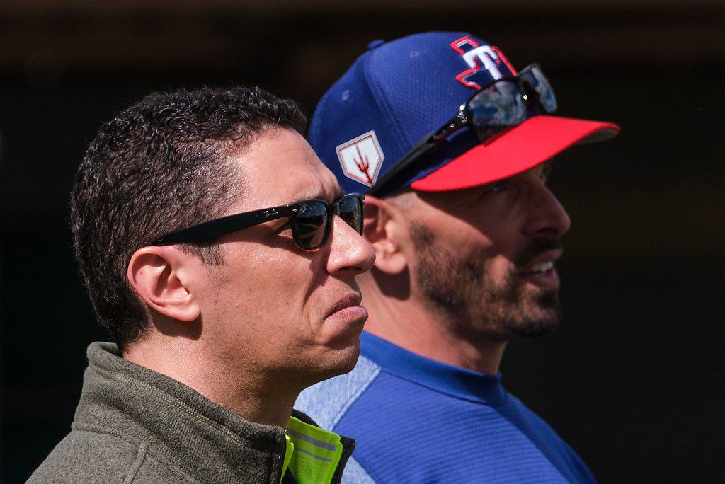 Texas Rangers President of Baseball Operations Jon Daniels (left) and manager Chris Woodward watch the on-field action during spring training in 2019.
