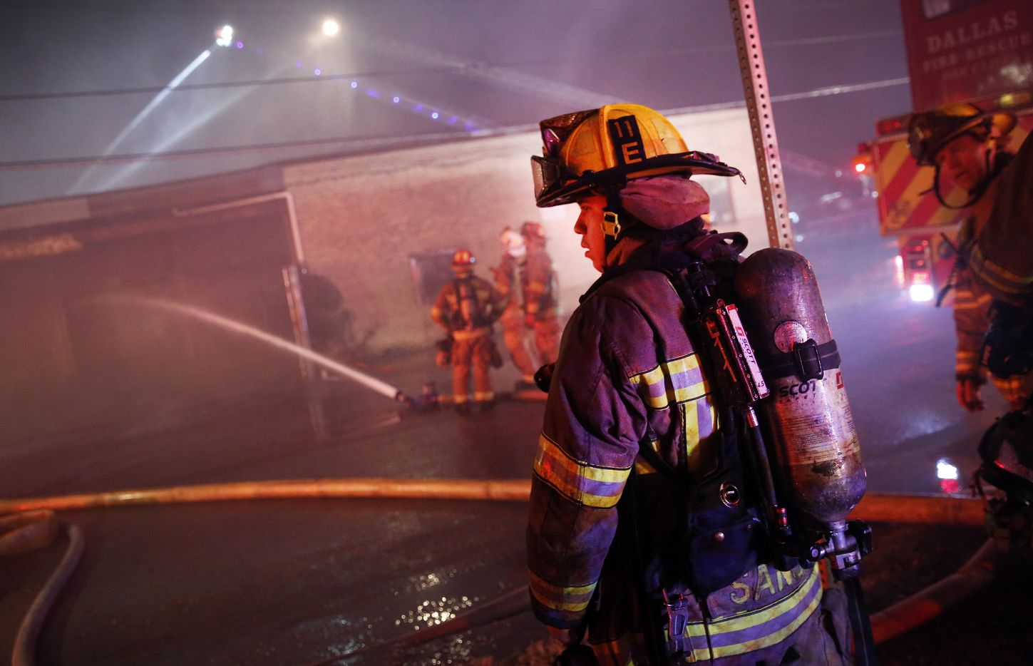 Dallas firefighters wait to join the battle of a four-alarm business fire in the Fair Park area, just south of Interstate 30 near the Austin Street Shelter, Wednesday, November 13, 2019. Smoke was seen rolling across Interstate 30 from the ORS Food Company. (Tom Fox/The Dallas Morning News)