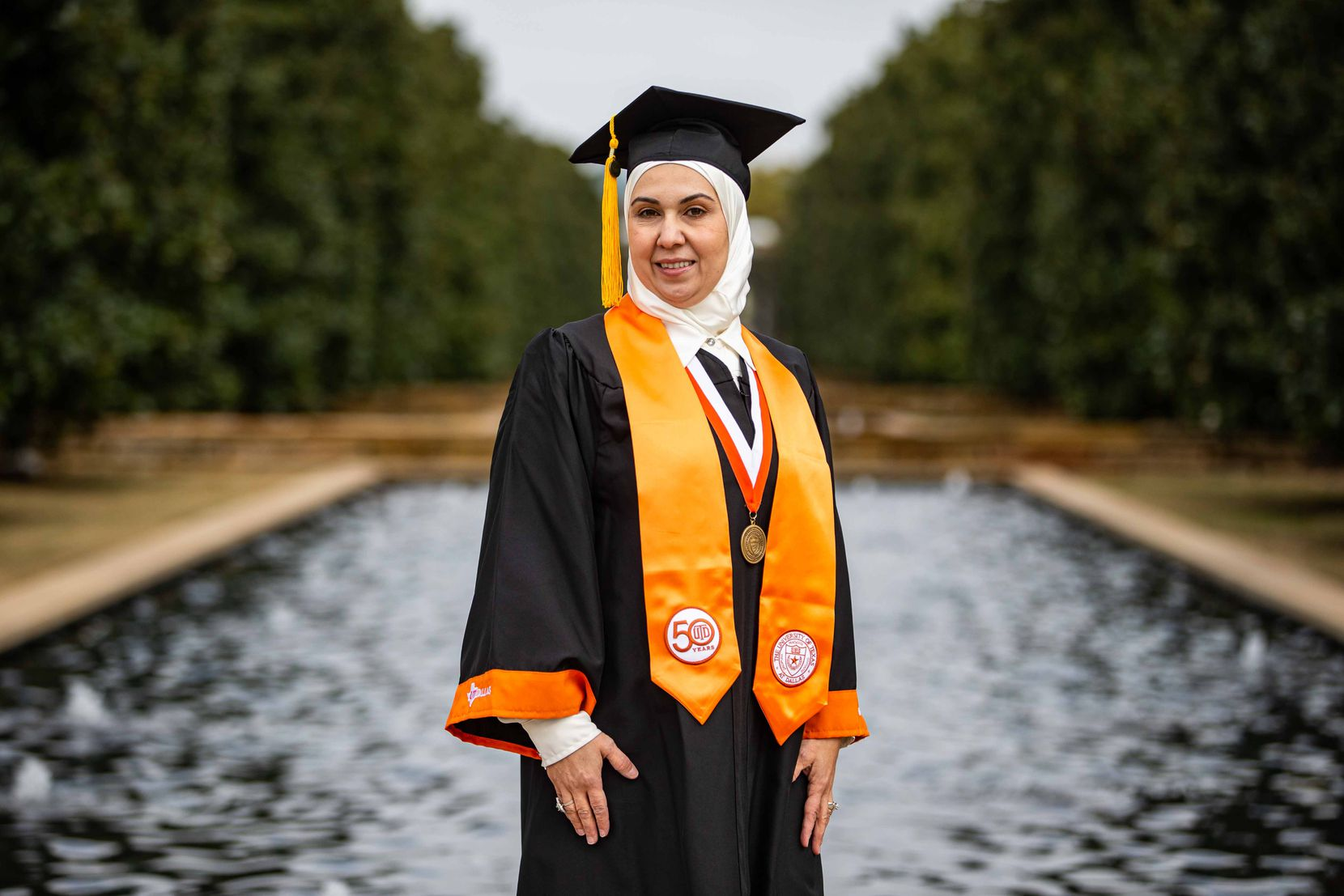 Ruba Kuzbari poses with her cap and gown at UTD. Kuzbari is graduating with a degree in public affairs and hopes to start a nonprofit after getting her master's degree at UTD in Richardson on Wednesday, December 16, 2020. (Lola Gomez/The Dallas Morning News)