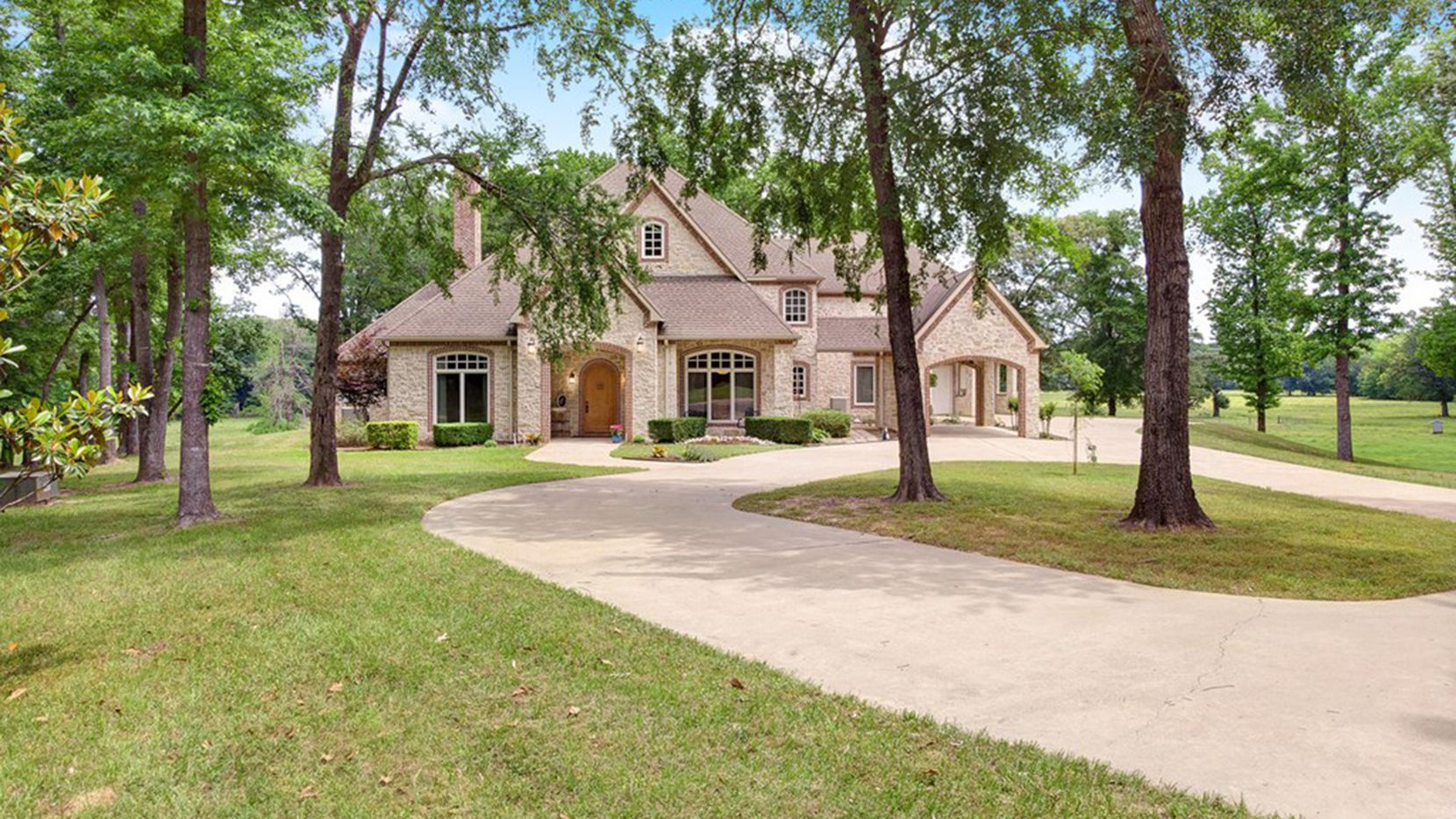 Spring-fed Bushy Creek and Norwegian Creek accent this East Texas ranch property, which includes a custom home and guest cabin.