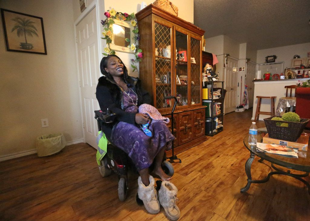 Mythia Joseph puts on warmer shoes as she sits in her motorized wheelchair, before venturing out through the intersection of Hall and Central Expressway on shopping trip to Walmart on March 15, 2017. (Louis DeLuca/The Dallas Morning News)
