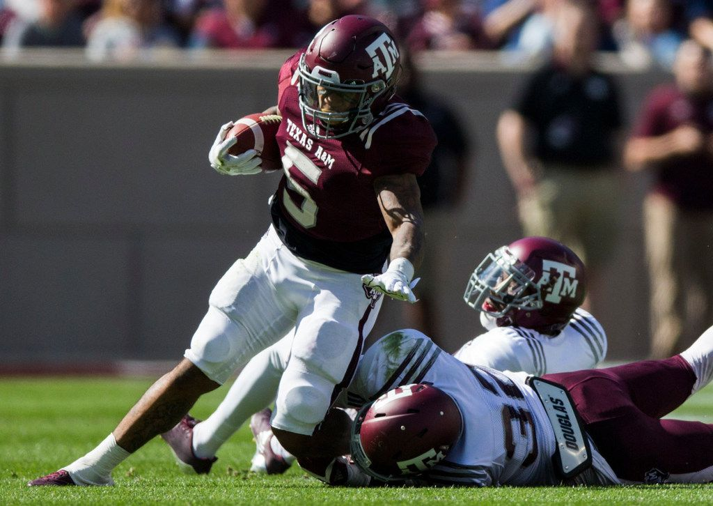 Texas A&M Aggies running back Trayveon Williams (5) is tackled by Texas A&M Aggies linebacker Santino Marchiol (32) during a Texas A&M University Maroon and White scrimmage football game on Saturday, April 14, 2018 at Kyle Field in College Station, Texas. (Ashley Landis/The Dallas Morning News)