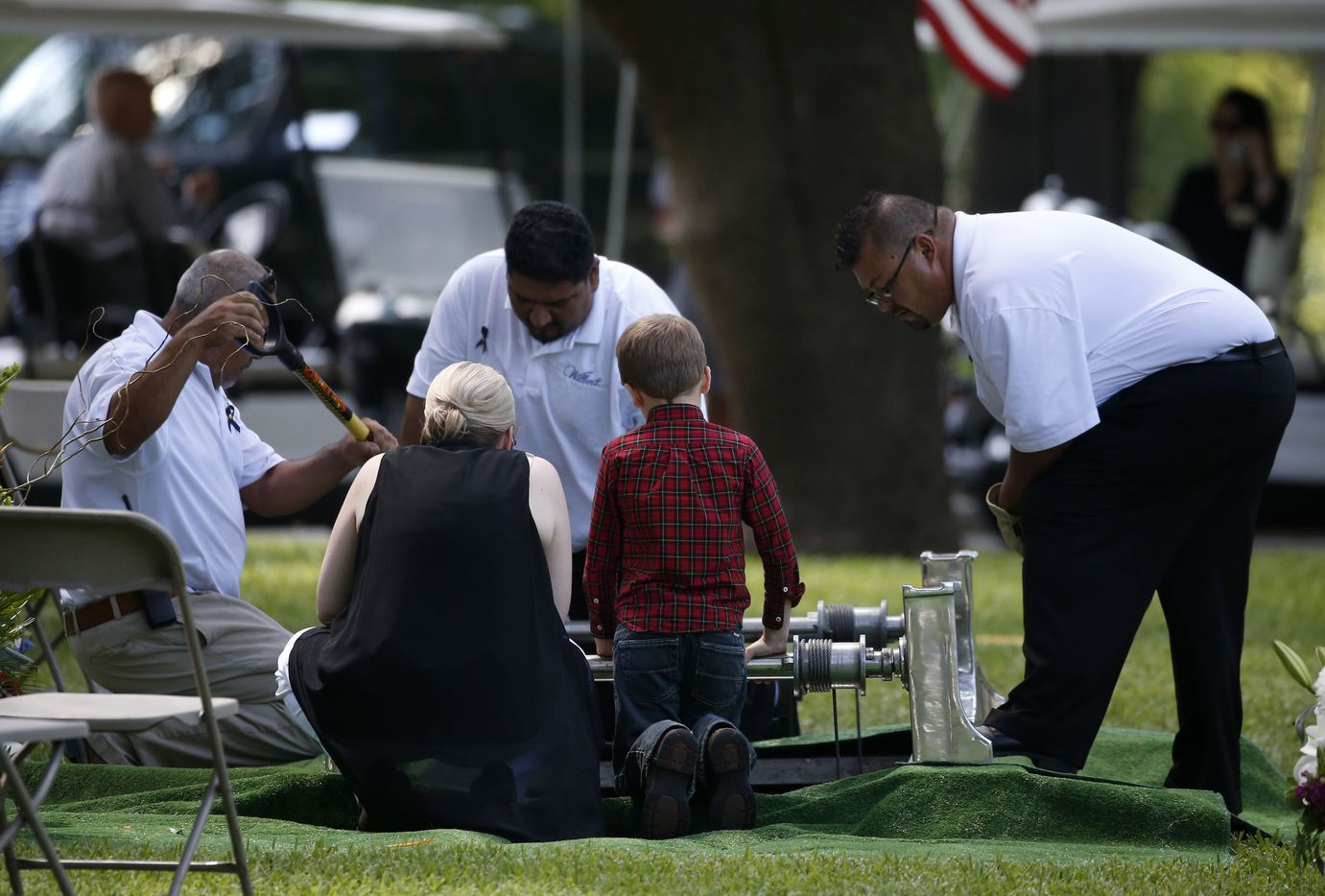 Katrina Ahrens, wife of fallen Dallas police officer Lorne Ahrens, kneels beside her son Magnus Ahrens, 8, at the burial for her husband in the Garden of Honor at Restland Funeral Home and Cemetery in Dallas on July 13, 2016. Ahrens and four other officers were gunned down during an ambush on police in downtown Dallas.