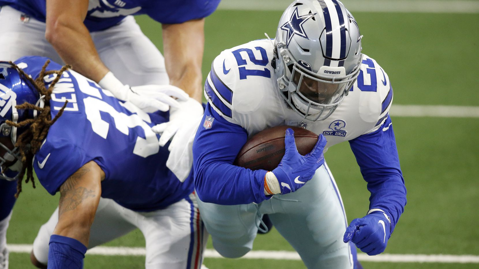 Dallas Cowboys running back Ezekiel Elliott (21) is hit by New York Giants running back Dion Lewis (33) after making a catch during the first quarter at AT&T Stadium Stadium in Arlington, Texas, Sunday, October 11, 2020.