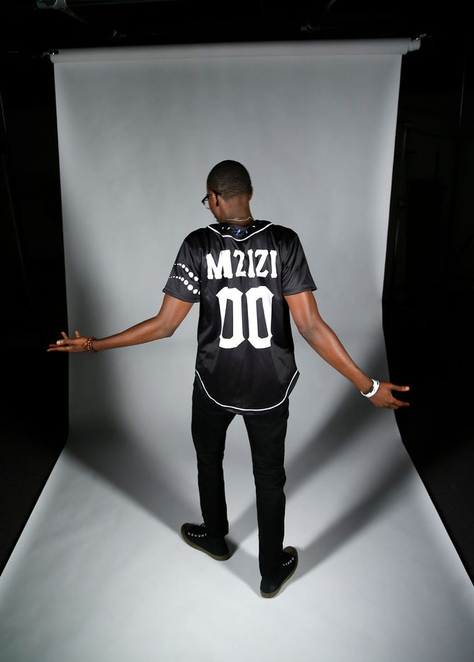 """Paakow Essandoh, co-founder and CEO of MIZIZI International, poses with the """"Black Panther"""" jersey in the Dallas Morning News studio."""