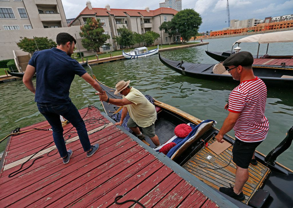 Dallas Morning News reporter Brendan Meyer, left, helps reader Ayhan Calis get off a gondola.