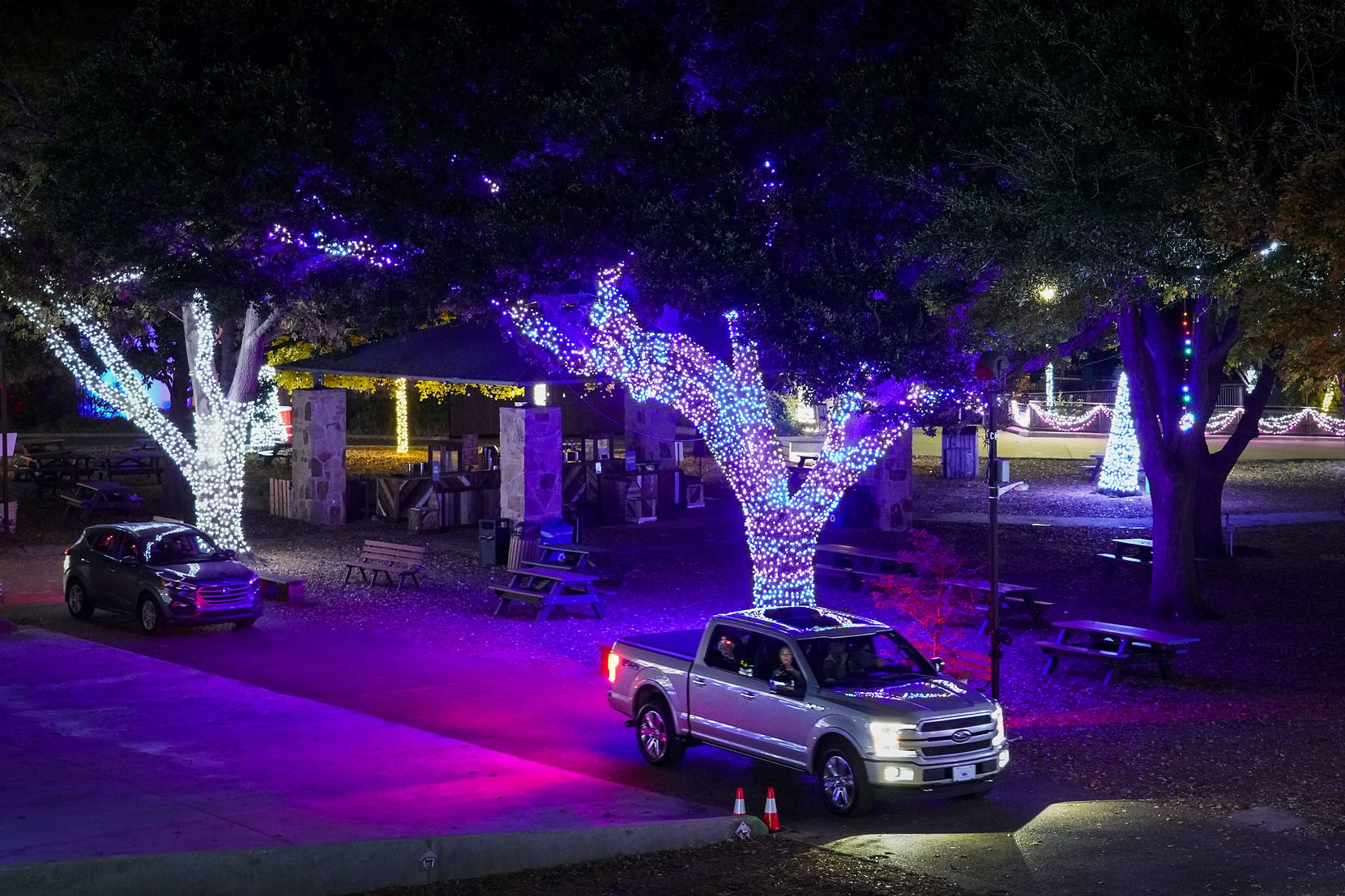 Motorists make their way through displays during Dallas Zoo Lights on Wednesday, Nov. 18, 2020, in Dallas. The Dallas Zoo?s display of one million lights and silk-covered, animal-shaped, lanterns is presented as a drive-through this year.  (Smiley N. Pool/The Dallas Morning News)