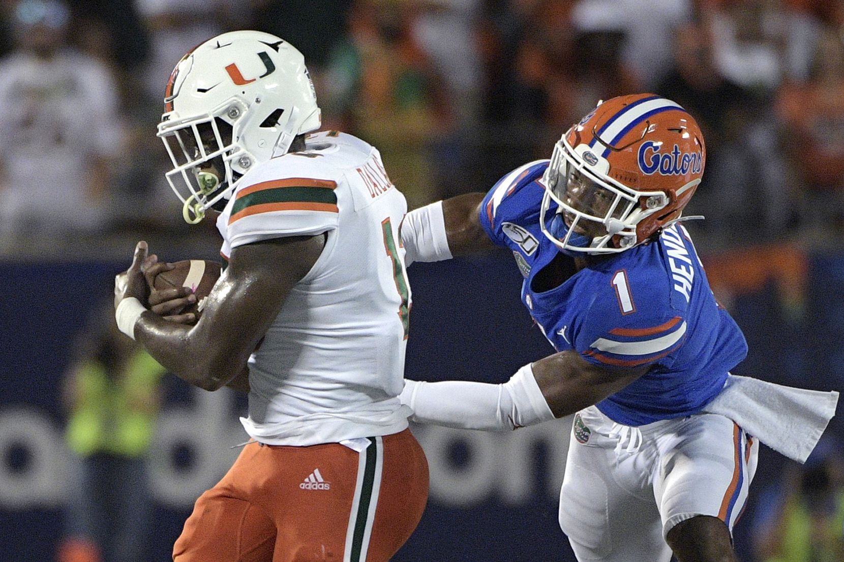 Miami running back DeeJay Dallas (13) rushes for yardage as Florida defensive back CJ Henderson (1) defends during the first half of an NCAA college football game Saturday, Aug. 24, 2019, in Orlando, Fla. (AP Photo/Phelan M. Ebenhack)