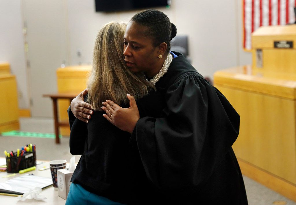 "State District Judge Tammy Kemp gives fired Dallas police officer Amber Guyger a hug before she leaves for jail. Kemp gave her one of her own Bibles and offered encouragement, saying she did so because Guyger ""has a lot of life to live."""