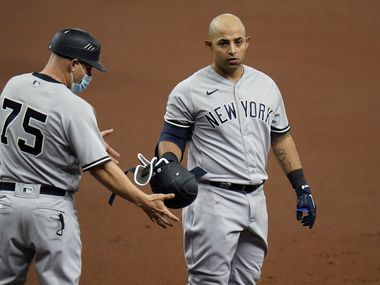 New York Yankees' Rougned Odor, right, hands his helmet to first base coach Reggie Willits after popping out against the Tampa Bay Rays during the second inning of a baseball game Sunday, April 11, 2021, in St. Petersburg, Fla.