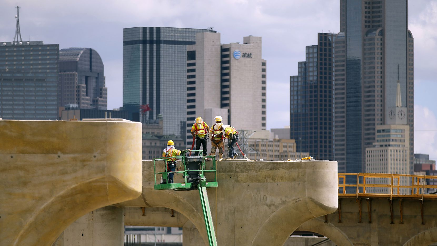 In 2014, construction crews worked atop the bridge support columns and tops of the new northbound Interstate 35E bridge leading to downtown Dallas, a part of the massive Dallas Horseshoe Project. The nearly $800 million design-build project was worked on by Pegasus Link Contractors, a joint venture between Fluor and Balfour Beatty.