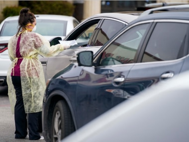 Office manager Kristy Castillo talks with a patient as cars line up for drive-thru coronavirus testing at Neighborhood Medical Center on Monday, March 16, 2020, in Dallas. Patients first were tested for flu and streptococcal infections at the center.
