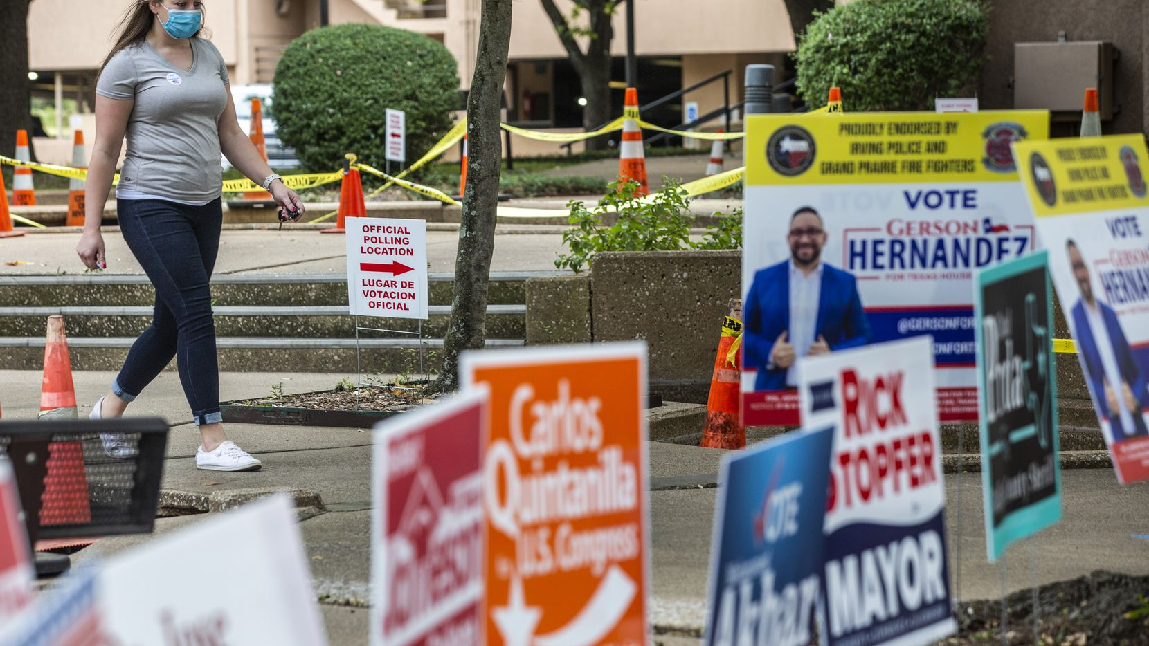 Alyse Brown walks past campaign signs after casting a ballot during the general election early voting period at Irving City Hall in Irv,ing, Texas on Wednesday, Oct. 21, 2020.