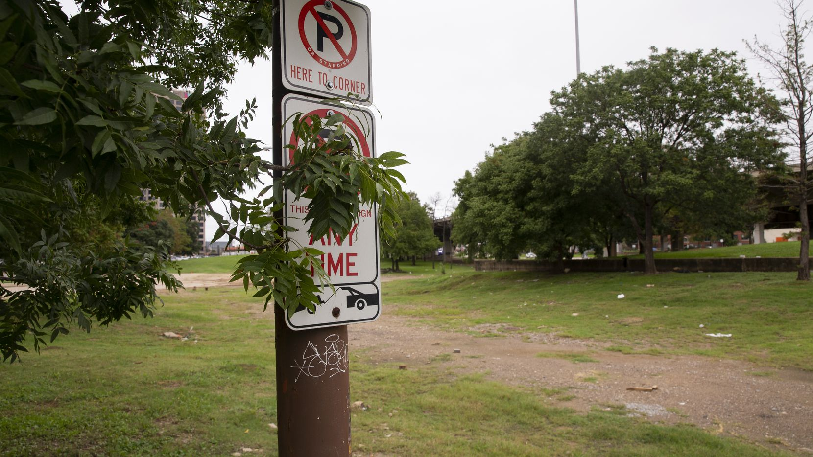 """No parking"" signs are still affixed to now-random light poles that once stood alongside streets before a major roads realignment on downtown Dallas' east side left the area a mishmash of weeds, mud and broken asphalt."