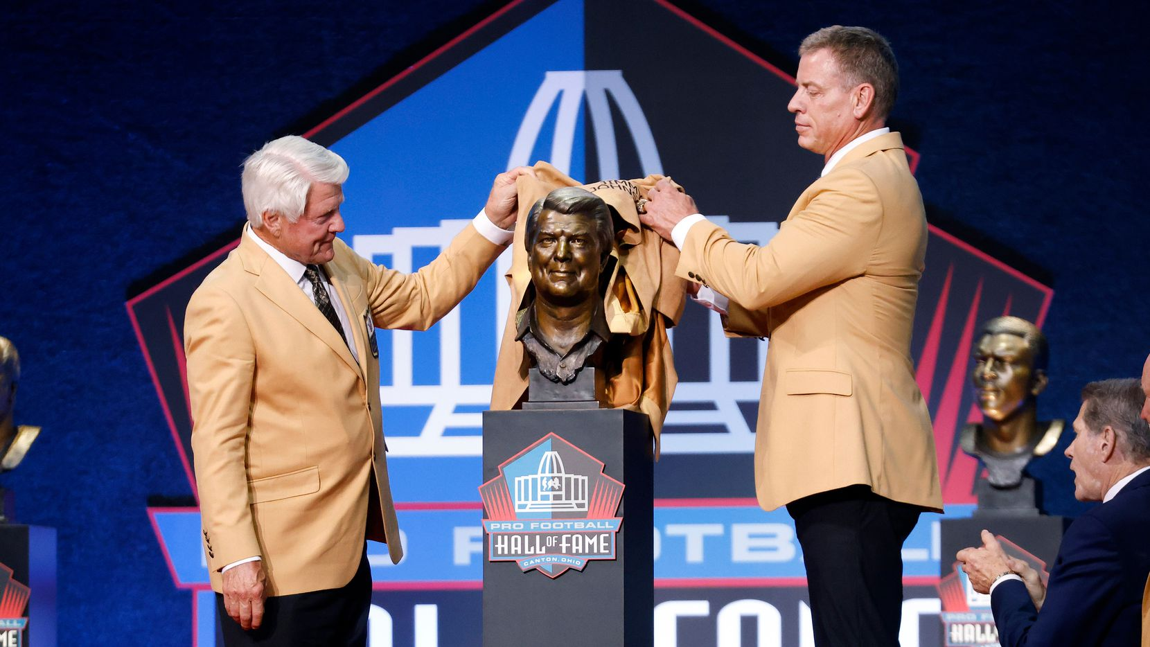 Pro Football Hall of Fame inductee Jimmy Johnson of the Dallas Cowboys (left) unveils his bronze bust with presenter and former Cowboy Troy Aikman during the Centennial Class of 2020 enshrinement  ceremony at Tom Benson Hall of Fame Stadium in Canton, Ohio, Saturday, August 7, 2021. (Tom Fox/The Dallas Morning News)