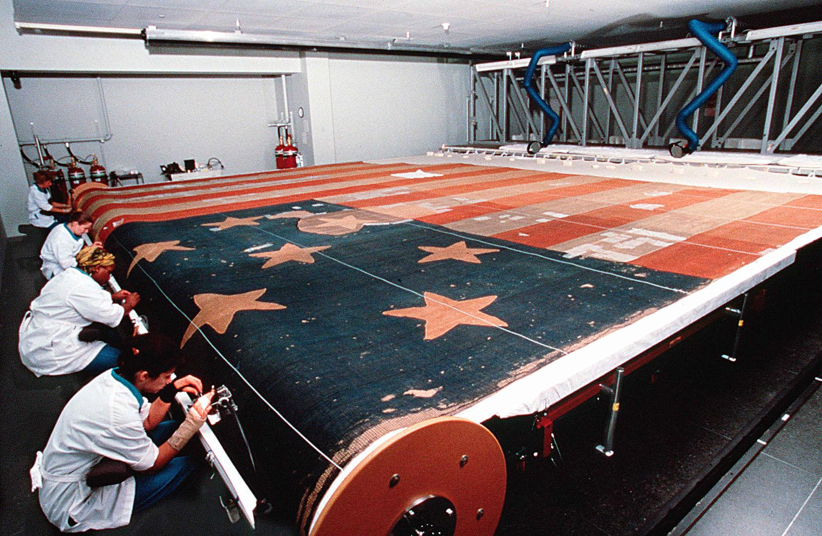 A photo released by Smithsonian Institution shows curators restoring the Star-Spangled Banner, the flag that inspired the words of the National Anthem, at the National Museum of American History. On June 14, 2001, Flag Day, conservators concluded that the 208-year-old flag was more fragile than originally believed and would have to be displayed to the public on a slight incline that would protect the fabric from stress.