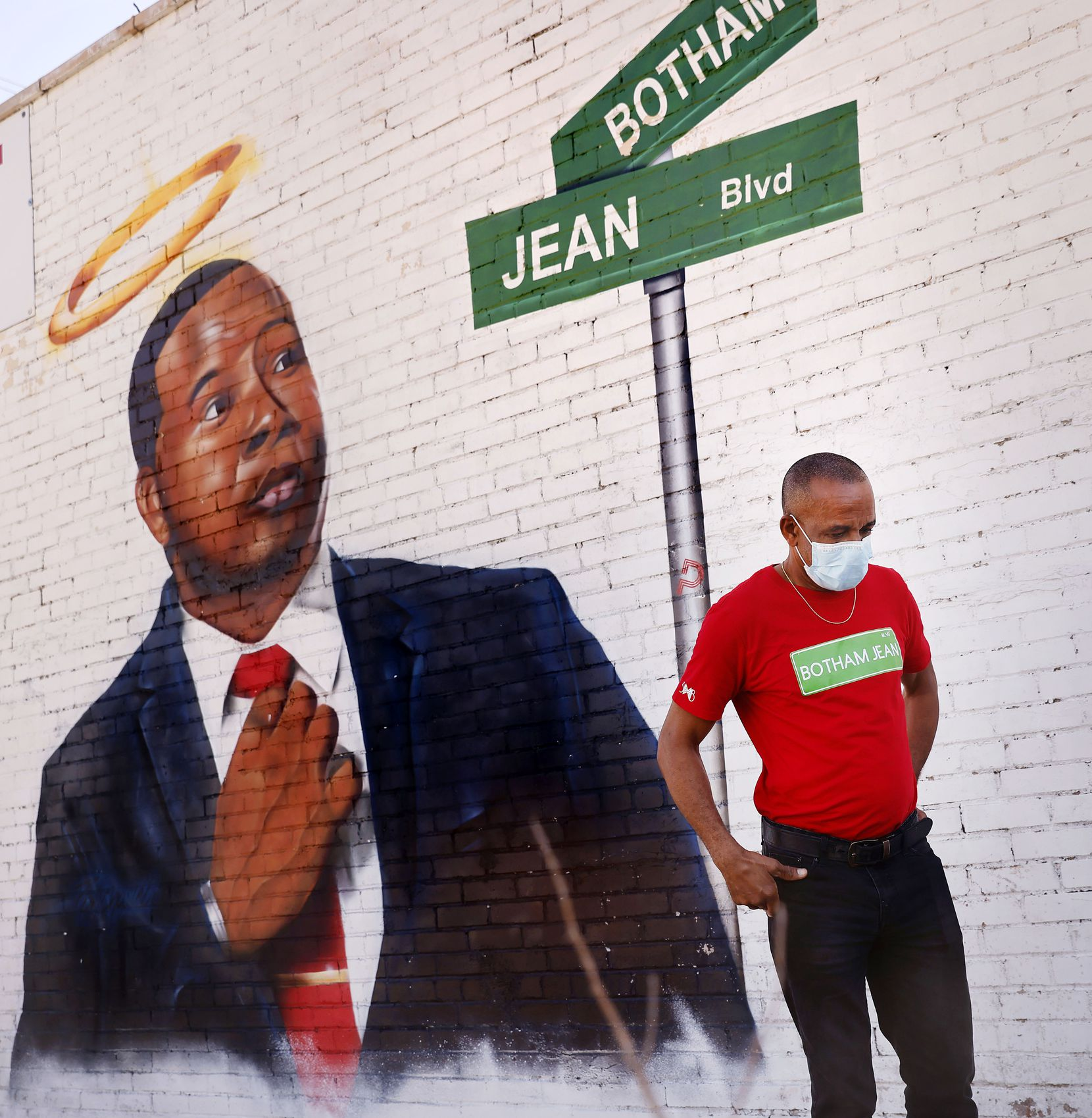 Bertrum Jean takes a moment for himself as he views a mural of his slain son, Botham Jean, on South Lamar Street. A part of the road will be renamed Botham Jean Boulevard on Saturday, March 27, 2021.