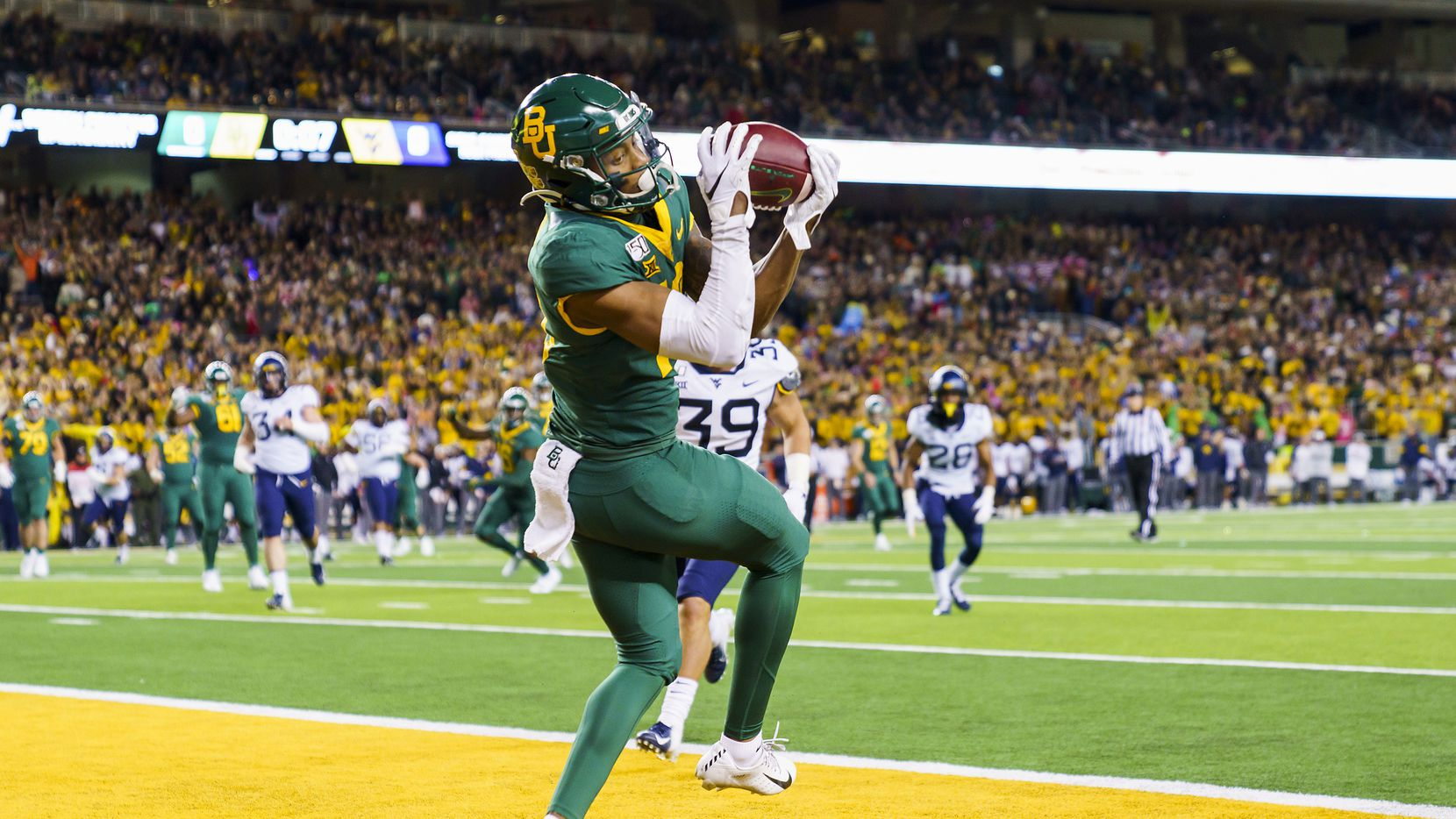 Baylor wide receiver R.J. Sneed (13) hauls in a 13-yard touchdown pass from quarterback Charlie Brewer during the first half of an NCAA football game against the West Virginia at McLane Stadium on Thursday, Oct. 31, 2019, in Waco, Texas.