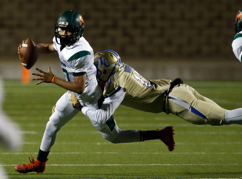 Naaman Forest QB Jayden Flores (17) is grabbed by Lakeview defender Gavin Harris (13) during the first half of their high school football game at Homer B. Johnson Stadium on Friday, November 8, 2019. (John F. Rhodes / Special Contributor)