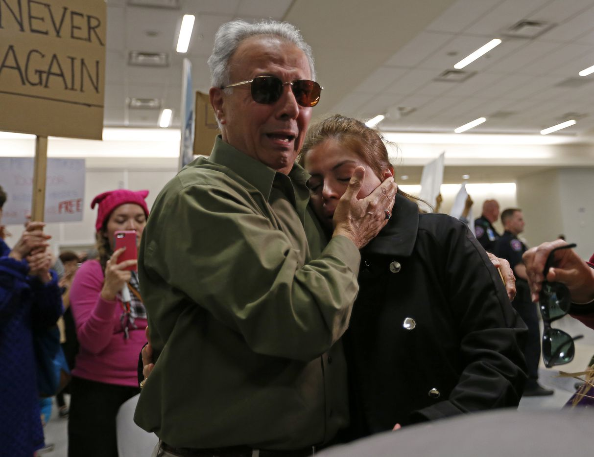 Iranian green card holder Shima Behgooy (right) cries on the shoulders of her father-in-law Ahmad Behgooy, a native of Iran who is now a naturalized U.S. citizen, after she was released from being held at Dallas/Fort Worth International Airport in Dallas, Saturday, Jan. 28, 2017. Shima's husband is a U.S. citizen. They live in Plano. Her mother who was traveling with her was sent back to Iran after they landed in Frankfurt, Germany.