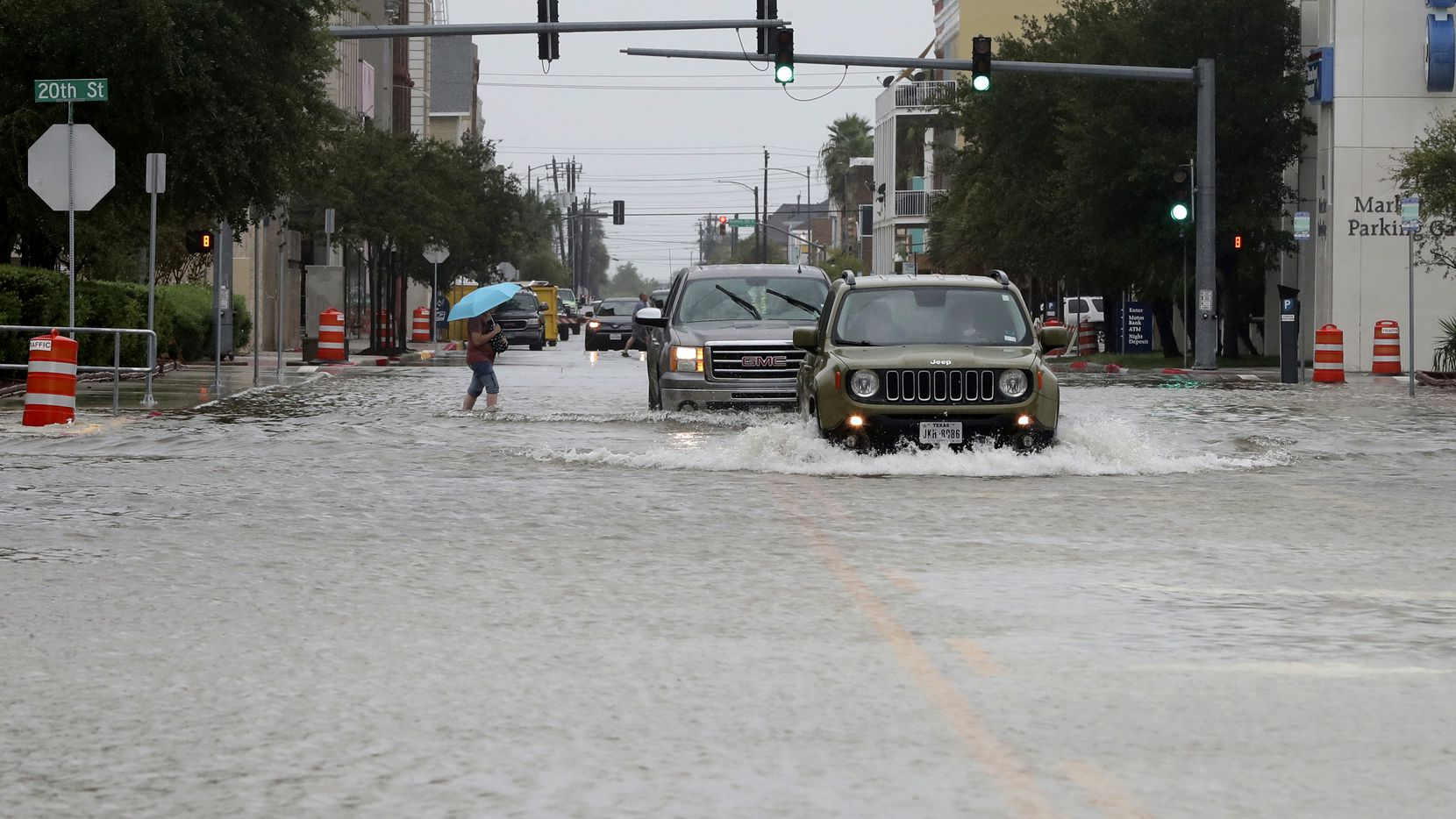 Cars make their way through high water at 20th and Market streets in Galveston on Friday.