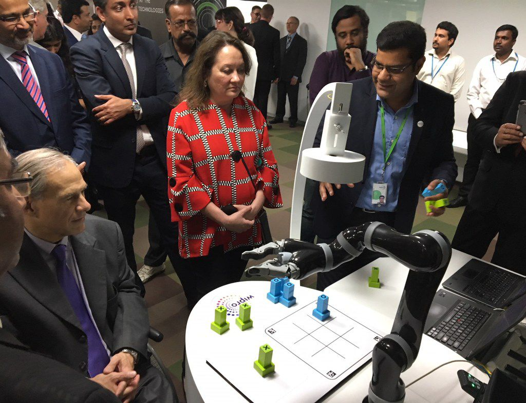 In 2018, Texas Gov. Greg Abbott played tic-tac-toe with a robot in Bengaluru, India, as Abidali Neemuchwala, then-CEO of Wipro, and first lady Cecilia Abbott watched.