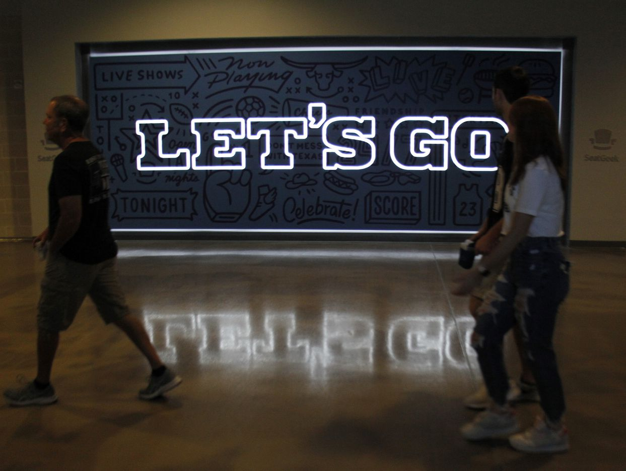 Dallas Cowboys fans walk past an illuminated sign as they make their way to seats to watch a team practice session. The Cowboys conducted their final public football practice session inside The Star at the Ford Center in Frisco on August 28, 2021. (Steve Hamm/ Special Contributor)