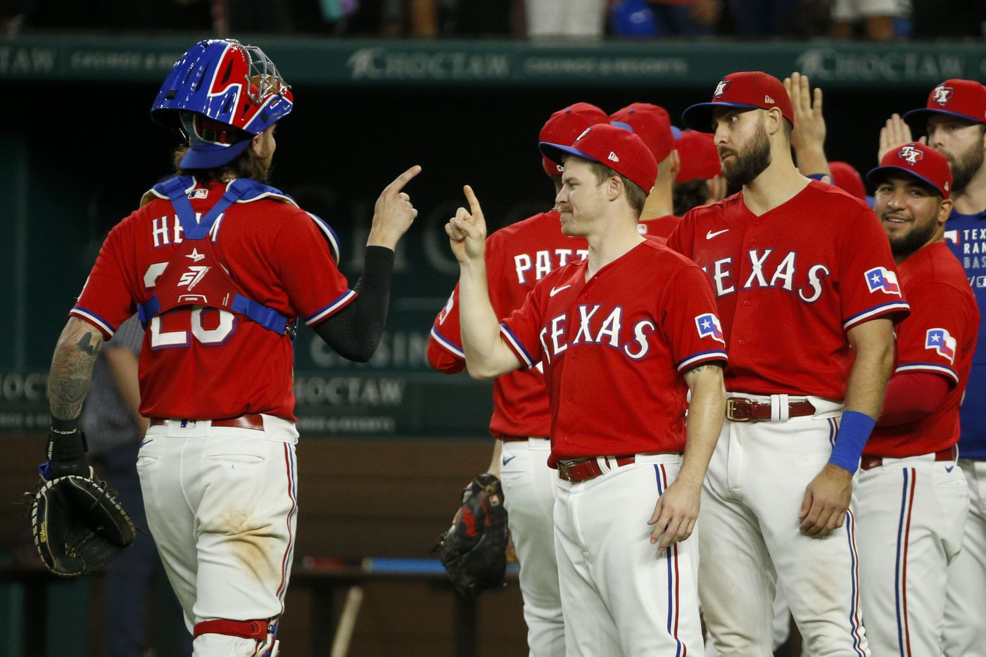 Texas Rangers catcher Jonah Heim (28) and second baseman Brock Holt (16) tap fingers after a 9-4 win over the Kansas City Royals at Globe Life Field on Friday, June 25, 2021, in Arlington. (Elias Valverde II/The Dallas Morning News)