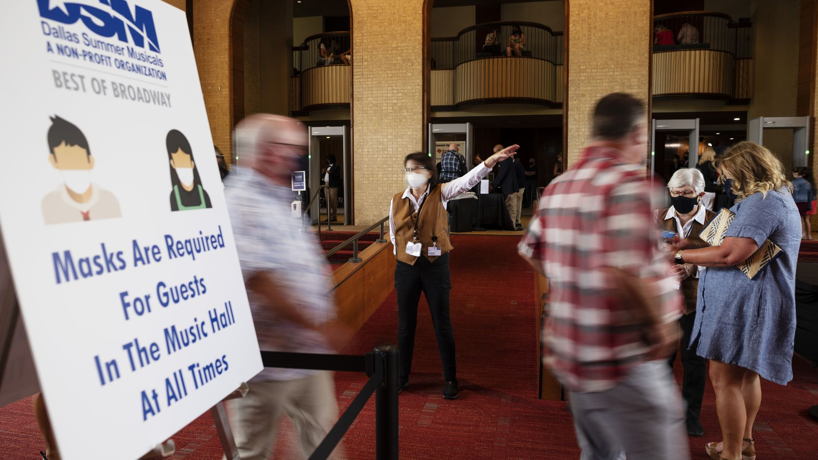 Signage at left informs patrons of the mask requirements inside the Music Hall at Fair Park as Joan Weltman, center, directs patrons for additional lines to enter a dress rehearsal of Wicked, hosted by Dallas Summer Musicals, on Sunday, Aug. 01, 2021 in Dallas.