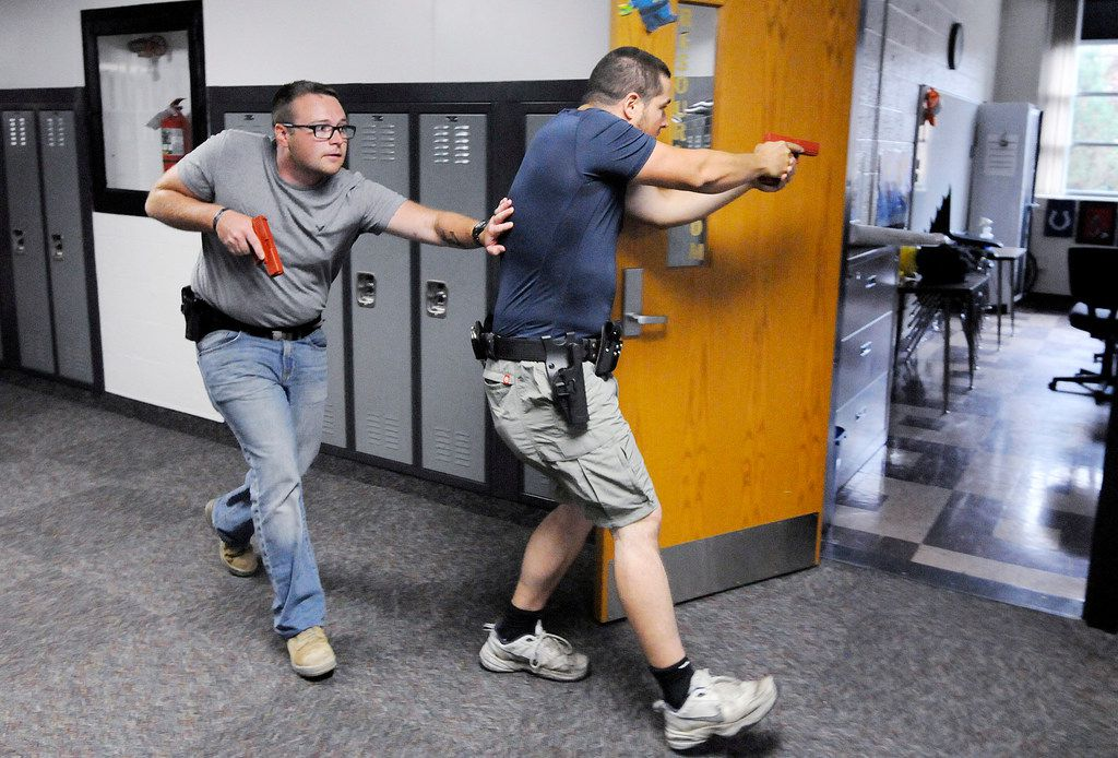 Justin Royse, left, and Dakota Steele practice moving down a hallway during active shooter training at Daleville High School in Daleville, Ind. on June 23, 2018. The training included local officers and teachers from the school district.