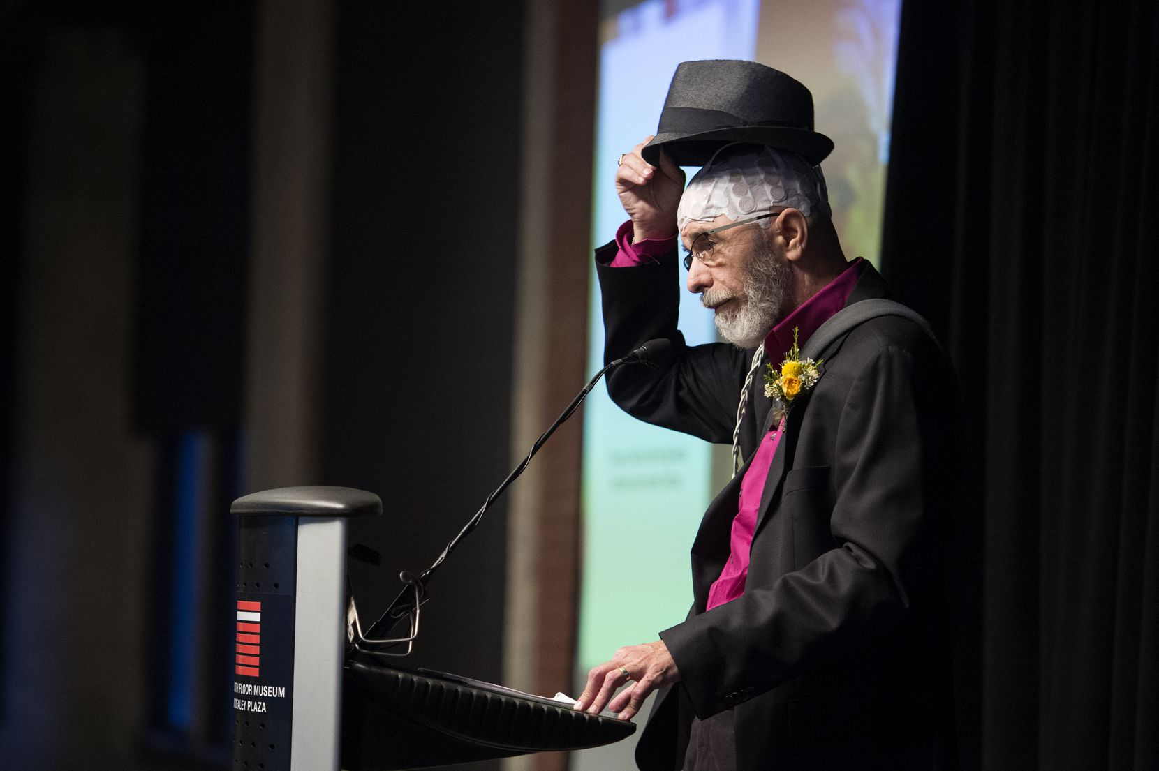 Longtime Dallas Morning News reporter Jeffrey Weiss, who is battling brain cancer, displays treatment apparatus during his acceptance speech at the Press Club of Dallas' North Texas Legends Awards ceremony on  June 3.