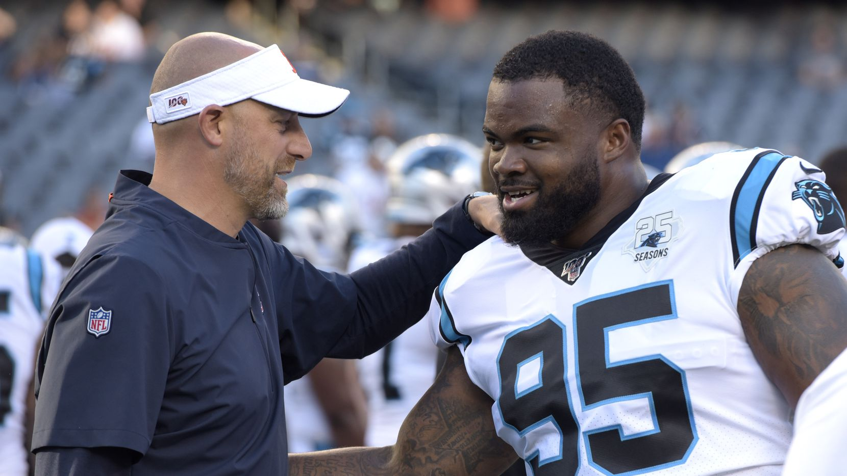 Chicago Bears head coach Matt Nagy, left, talks with Carolina Panthers' Dontari Poe before an NFL preseason football game Thursday, Aug. 8, 2019, in Chicago.