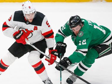 Dallas Stars center Radek Faksa (12) and New Jersey Devils left wing Taylor Hall (9) battle for control during the second period of a National Hockey League match between the Dallas Stars and the New Jersey Devils on Tuesday, Dec. 10, 2019 at American Airlines Center in Dallas.