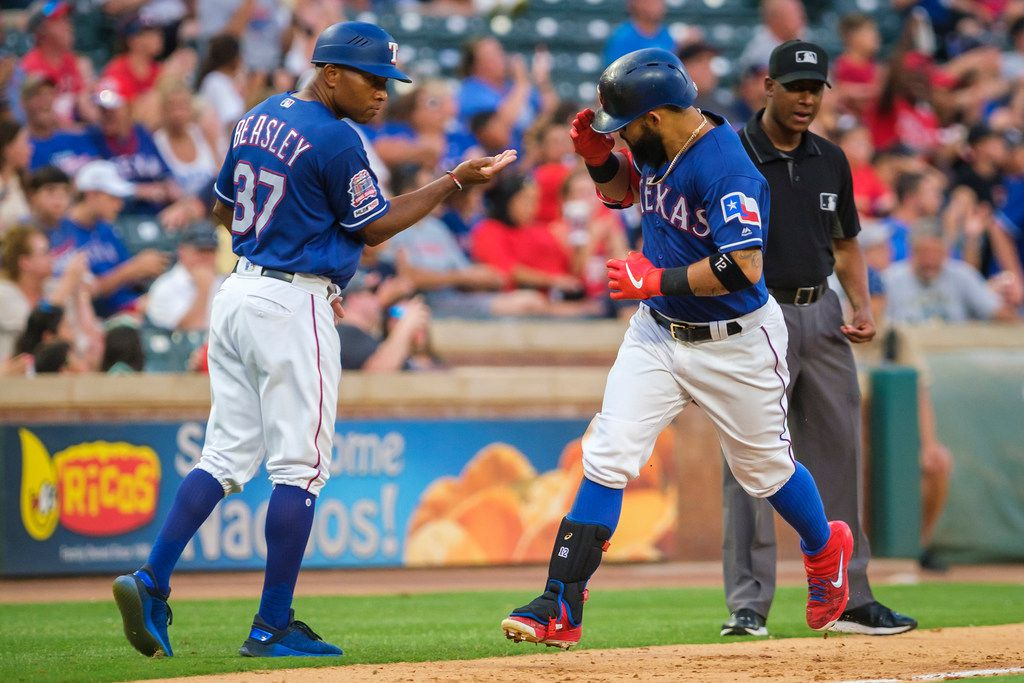 Texas Rangers second baseman Rougned Odor salutes third base coach Tony Beasley (37) as he rounds the bases after hitting a solo home run during the fourth inning against the Detroit Tigers at Globe Life Park on Friday, Aug. 2, 2019, in Arlington. (Smiley N. Pool/The Dallas Morning News)