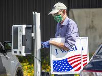Election poll worker Daryl Hinshaw wheels a curbside voting machine to a parked voter during the early voting period for the general U.S. election at Fretz Park Public Library in Dallas on Tuesday, Oct. 20, 2020. On Wednesday, Dallas County named a new elections administrator. (Lynda M. González/The Dallas Morning News)