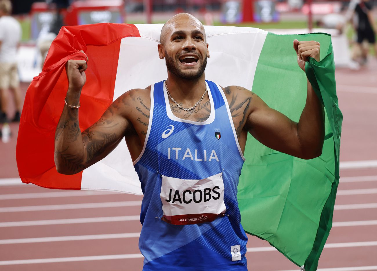 Italy's Lamont Marcell Jacobs celebrates after competing in the men's 100 meter final during the postponed 2020 Tokyo Olympics at Olympic Stadium, on Sunday, August 1, 2021, in Tokyo, Japan. Jacobs took first for gold with time of 9.80 seconds. (Vernon Bryant/The Dallas Morning News)