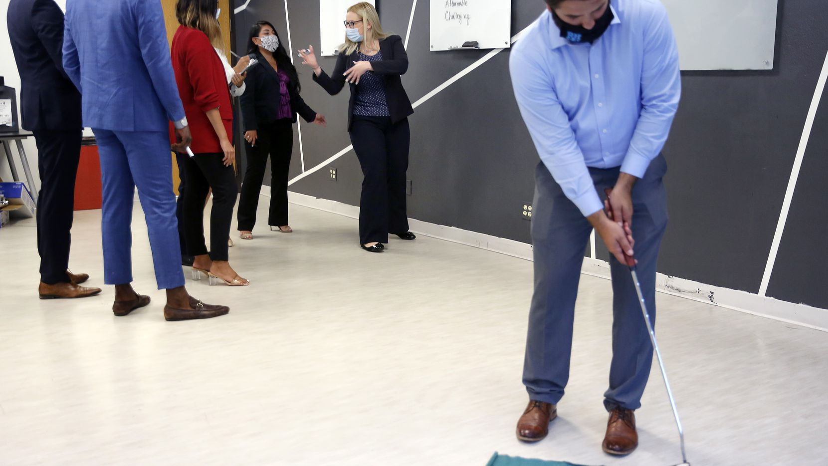 Lumos Marketing Group employees work on a team-building exercise as account executive Pierce Kopinski practices his putting at the company's Dallas office on Aug. 28.