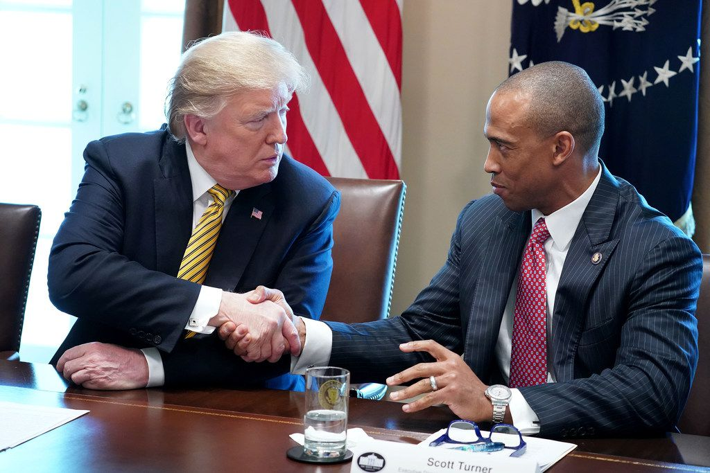 President Donald Trump shakes hands with White House Opportunity and Revitalization Council Executive Director Scott Turner.
