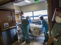 "Samantha Rowley (right), senior vice president of nursing and surgical services and the executive in charge of the Tactical Care Unit, watches as a group of nurses and respiratory therapist work to move a critically ill patient into the intensive care unit in the Parkland Hospital COVID-19 Tactical Care Unit on Wednesday, Aug. 26, 2020 in Dallas. For almost six months, many of the TCU caregivers have sustained their own daily trauma from dealing with so much death and despair, Rowley said. ""It's like death by paper cuts."" (Lynda M. González/The Dallas Morning News)"