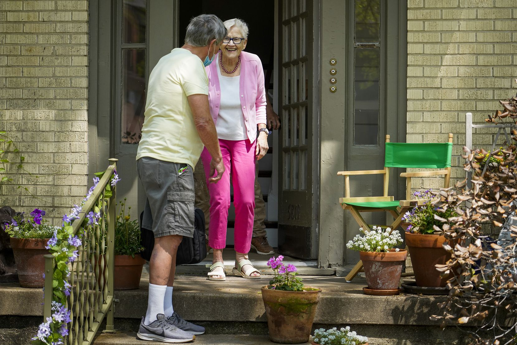 Vic Colon greets neighbor Jane Barker on her porch.
