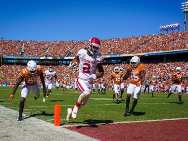 Oklahoma wide receiver CeeDee Lamb (2) scores on a 51-yard pass play past Texas defensives back B.J. Foster (25) and Chris Brown (15) during the second half of an NCAA football game at the Cotton Bowl on Saturday, Oct. 12, 2019, in Dallas. Oklahoma won the the game 34-27. (Smiley N. Pool/The Dallas Morning News)