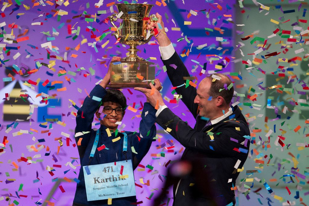 Karthik Nemmani, 14, from McKinney, Texas, is presented with the Scripps National Spelling Bee trophy by Adam Symson, president and CEO, E.W. Scripps Company, after he won the bee, in Oxon Hill, Md., Thursday, May 31, 2018.