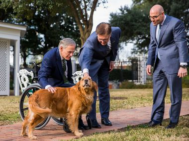 Gov. Greg Abbott (left) and House Speaker Dennis Bonnen pet one of the governor's dogs, Pancake, after a news conference with Lt. Gov. Dan Patrick (center) Wednesday at the governor's mansion.