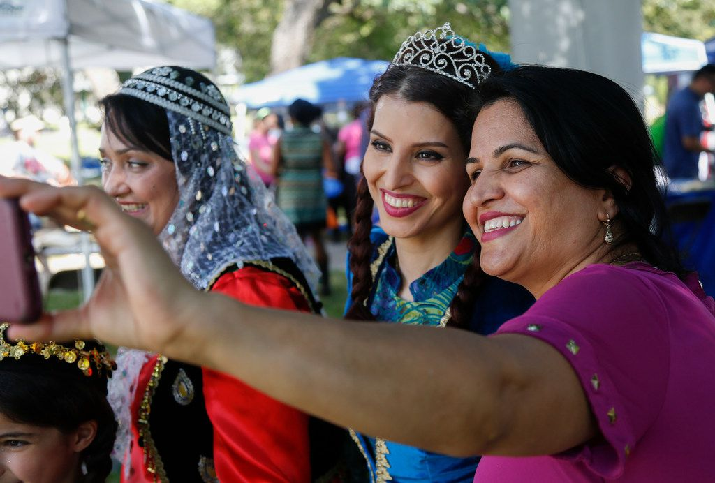 Banoo Irani, center, and Hajar Saufi, right, pose for a selfie before representing Iran in a fashion show at the Plano International Festival.