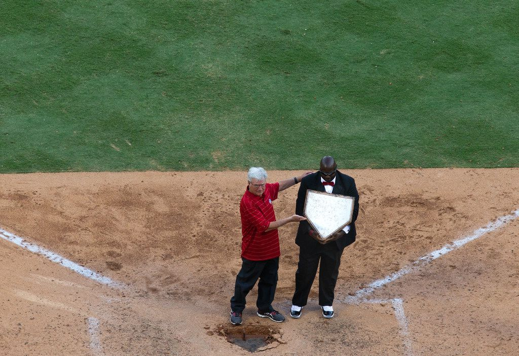 Former Arlington Mayor Richard Greene (left) and groundskeeper Devo Spencer lift up home plate following the Texas Rangers' final game ever played at Globe Life Park in Arlington, Texas, on Sunday, Sep. 29, 2019. Greene and Spencer ceremoniously moved the home plate to the new, adjacent Globe Life Field.