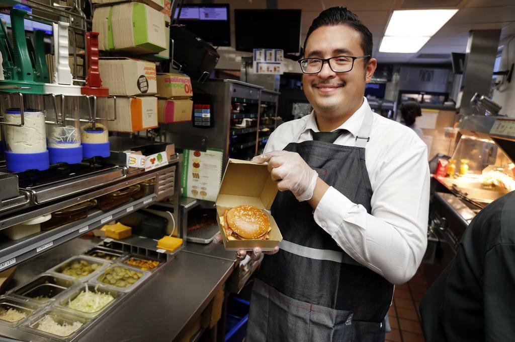 Carlos Soto, gerente de un McDonald's en Burleson, muestra el nuevo producto internacional: una McExtreme Bacon Burger. (DMN/TOM FOX)