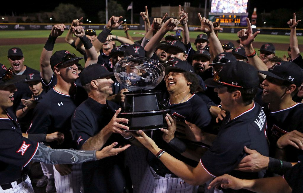 Texas Tech coach Tim Tadlock and Cameron Warren (11) hoist the Big 12 Conference championship Trophy after the team's win over TCU during a college baseball game Saturday, May 18, 2019, in Lubbock, Texas. (Sam Grenadier/Lubbock Avalanche-Journal via AP)