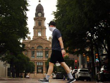 Wearing a mask, Matthew Lubinski of Bedford walks through downtown Fort Worth past the old Tarrant County Courthouse, Thursday, July 2, 2020.  As cases of the coronavirus surge to record highs, Gov. Greg Abbott on Thursday ordered Texans to wear face masks in public in counties with outbreaks of COVID-19. Abbott also gave local officials power to restrict outdoor gatherings with more than 10 people ahead of the holiday weekend.
